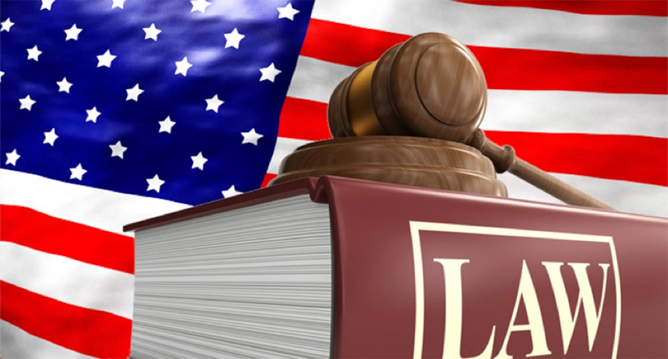 American flag, gavel and large book with Law typed on spine