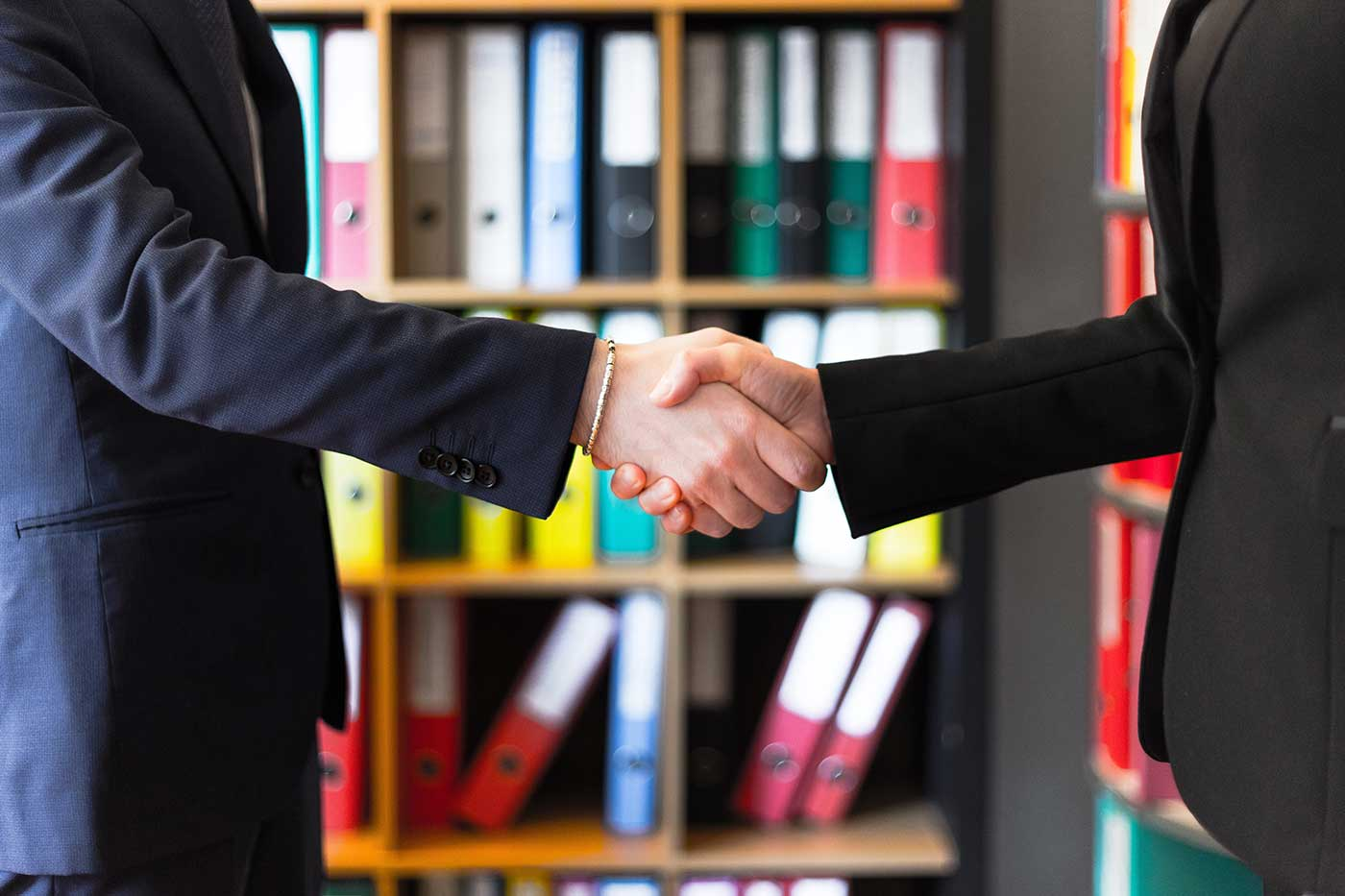 two people in suits shaking hands in front of book shelf
