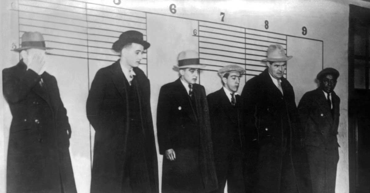 men wearing black coats and hat in black and white photo