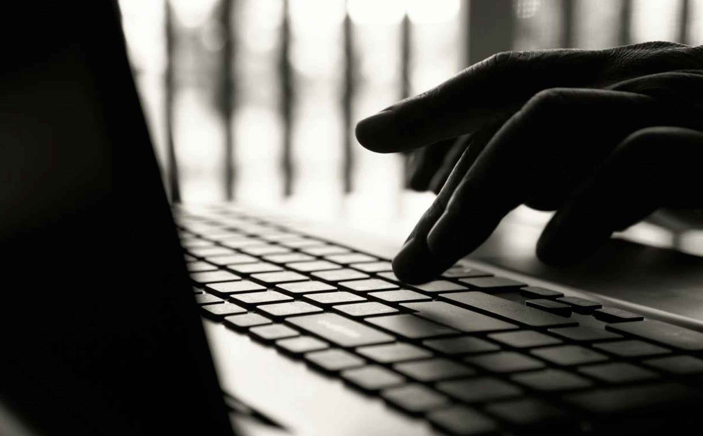 black and white picture - hand typing on a laptop keyboard